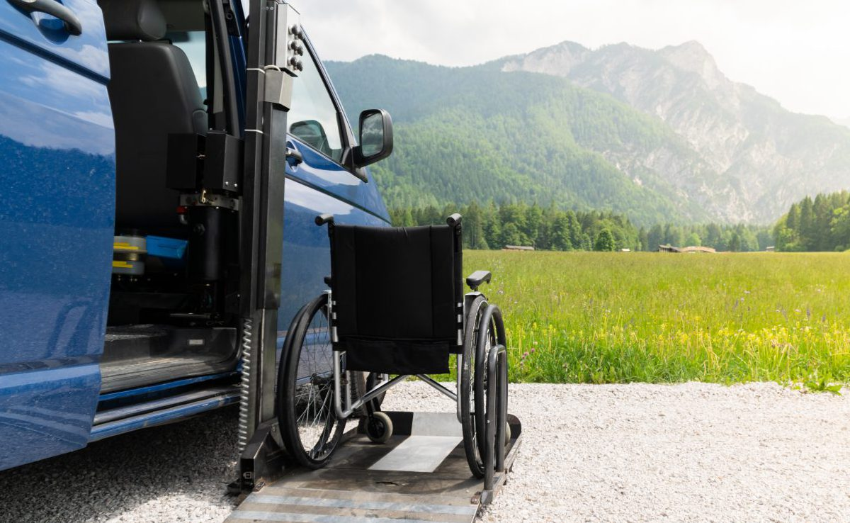 Photo of black electric lift specialized vehicle for people with disabilities. Empty wheelchair on a ramp with nature and mountains in the back
