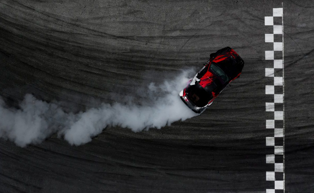Ariel view of a car drifting on a race track
